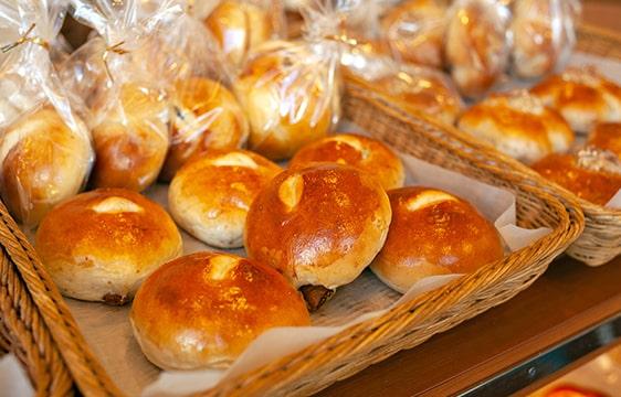 平たい籠の中に並ぶパンの画像