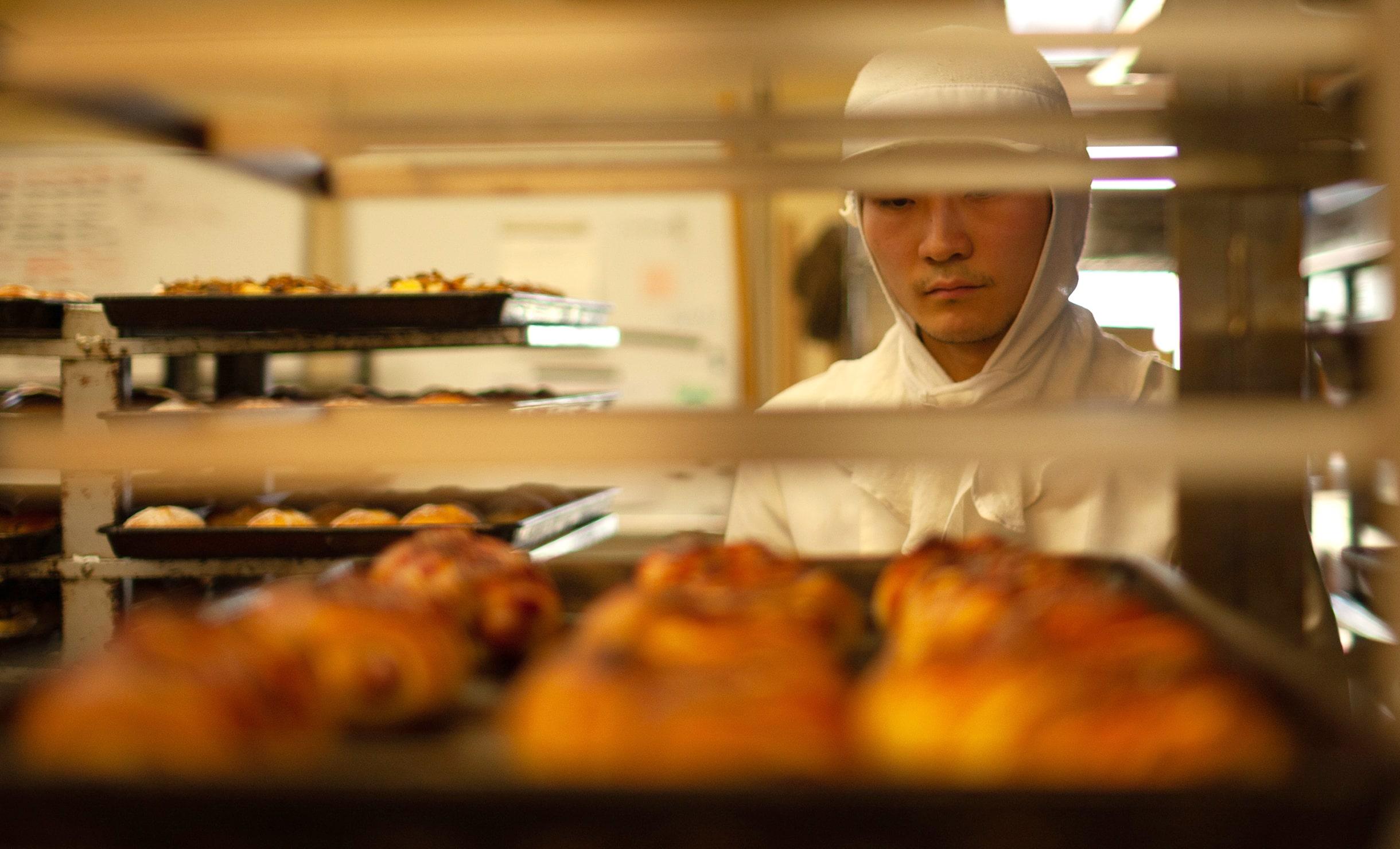 焼きたてのパンを眺める作業員の画像